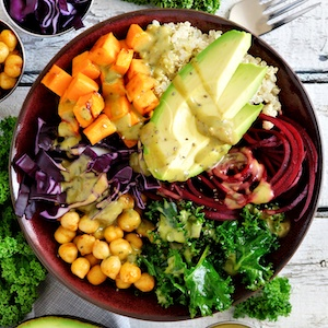 Buddha bowl with quinoa, avocado, chickpeas, vegetables on a white wood background
